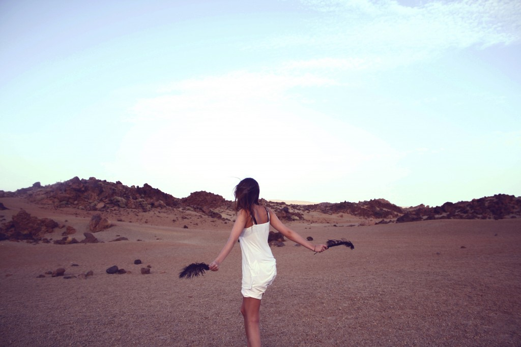 girl in desert with feathers